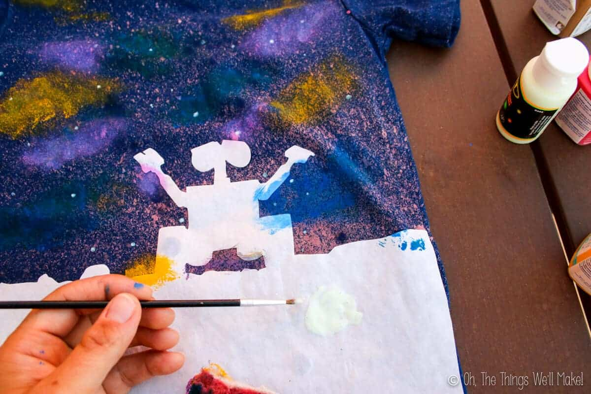 Closeup of t-shirt as starts are being painted around the freezer paint stencil of Wall-E's silhouette
