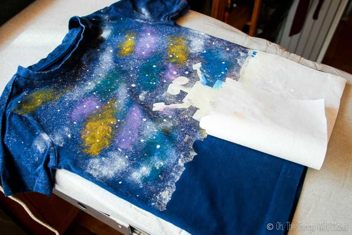 Removing the freezer paper stencil of Wall-E's silhouette to reveal the dark navy unpainted t-shirt below.