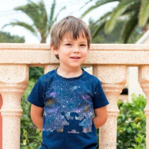 Boy wearing a t-shirt with a silhouette of Wall-E and a starry background.