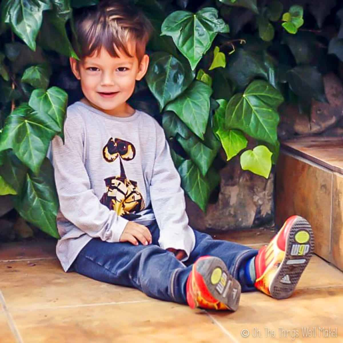 A young boy sitting on the ground wearing a wall-E t-shirt