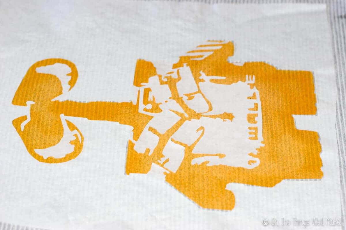 Wall-E freezer paper stencil over yellow painted layer, ready for painting layer 2