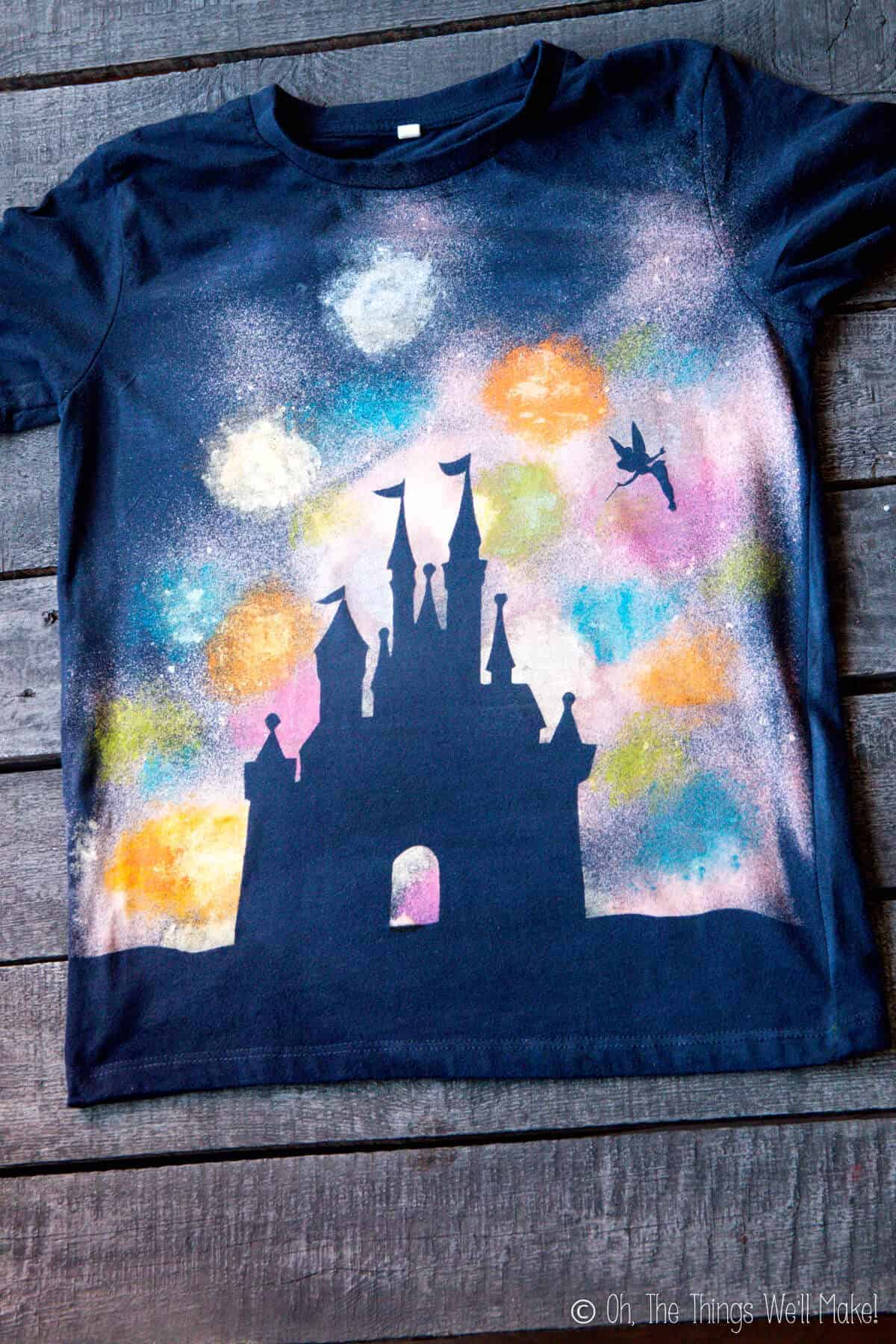 Navy Blue t-shirt featuring a silhouette of a Disney castle and Tinkerbell flying by it as seen against painted fireworks