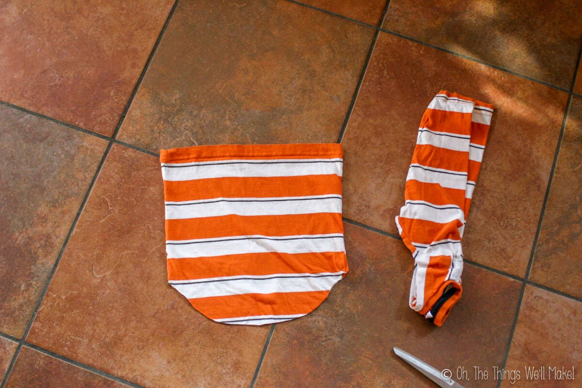 Top view of cut off sleeves off a striped orange and white t-shirt. This will be used to make a drawstring backpack.