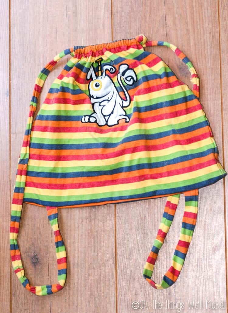 Top view of a finished drawstring backpack made from a baby shirt.