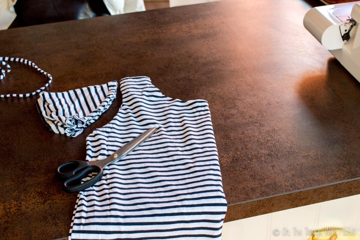 A striped t-shirt folded in half placed on a wood table, with sleeves and neck cut off.