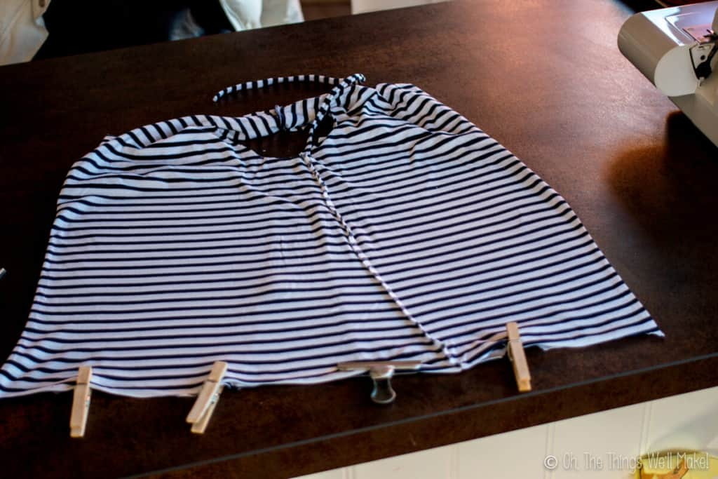 Striped t-shirt bag prepped for sewing with clothespins placed at the bottom of the bag to hold the seam in place.