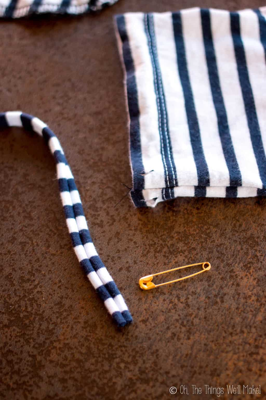 Close-up of cut slits in the hem of t-shirt drawstring pouch with a gold safety pin and striped strap beside it.