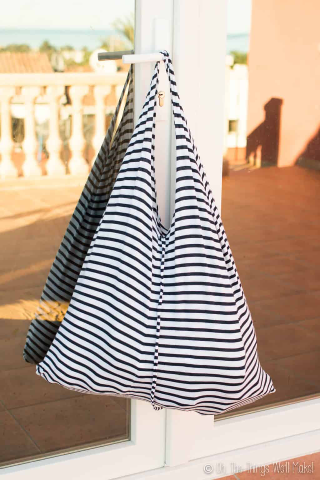 Finished striped white and black t-shirt bag hanging on a white glass door outside.