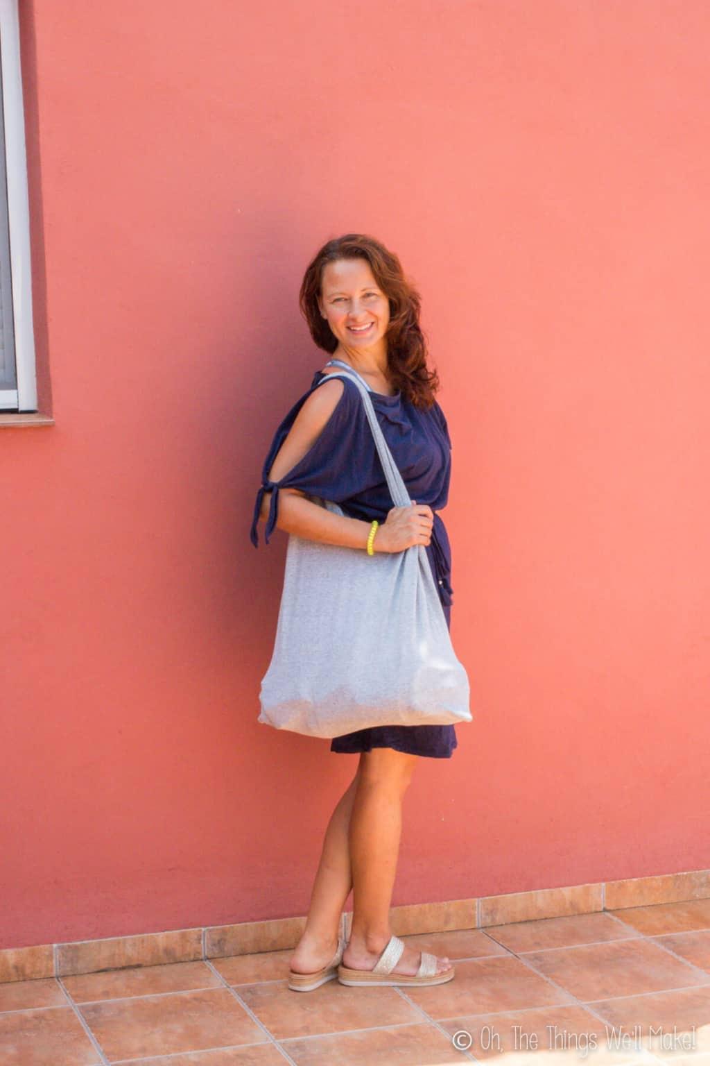 A caucasian woman smiling wearing a navy blue dress showing off her handmade striped t-shirt bag.