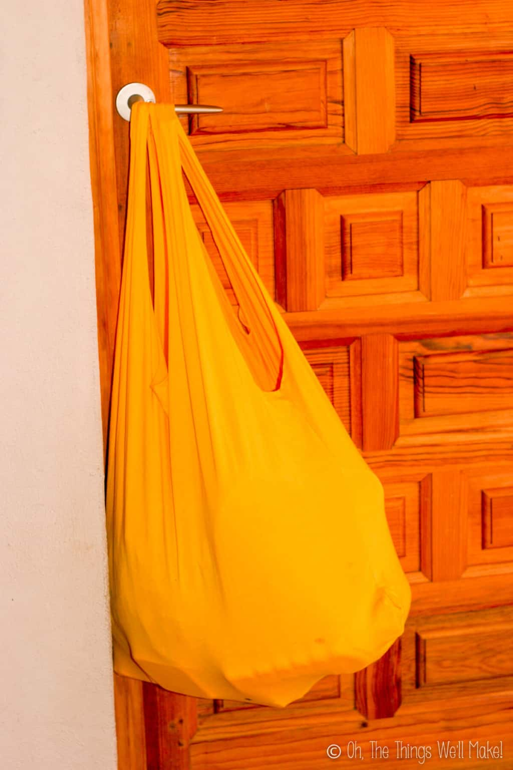 An orange t-shirt bag hanging on a door knob, filled with lots of heavy groceries.