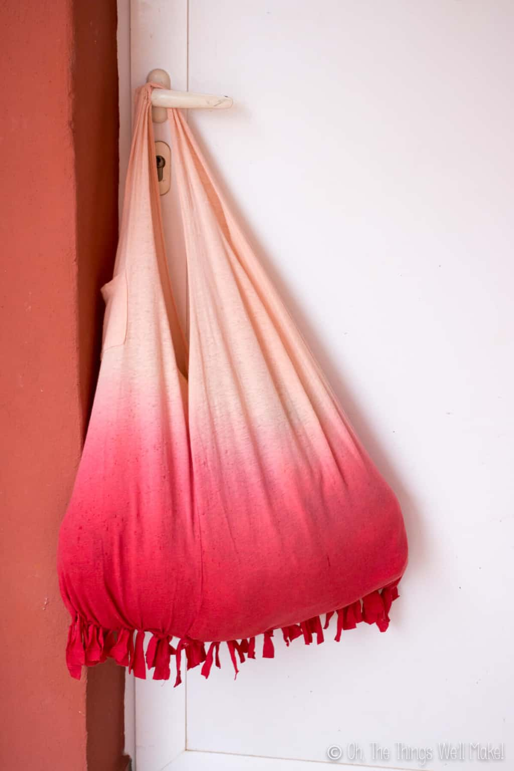 An ombre peach red no sew fringed bottom t-shirt bag hanging on a door knob of a white door.