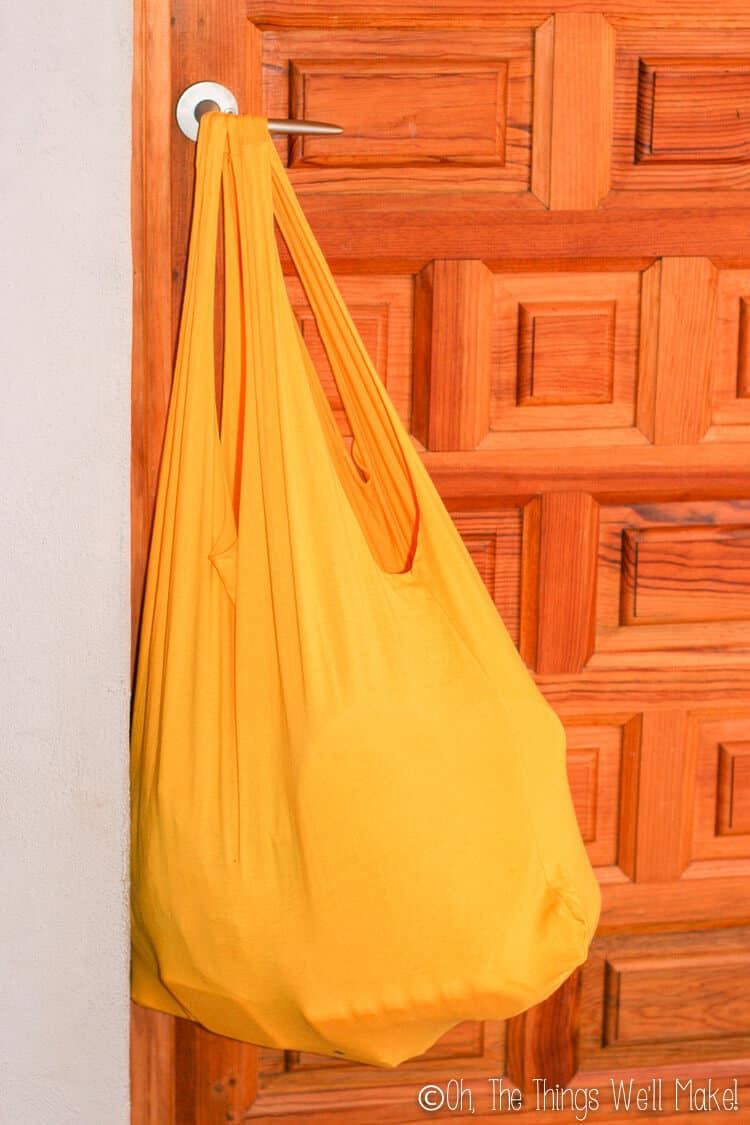 t-shirt bag filled with lots of heavy groceries, hanging on a door knob.