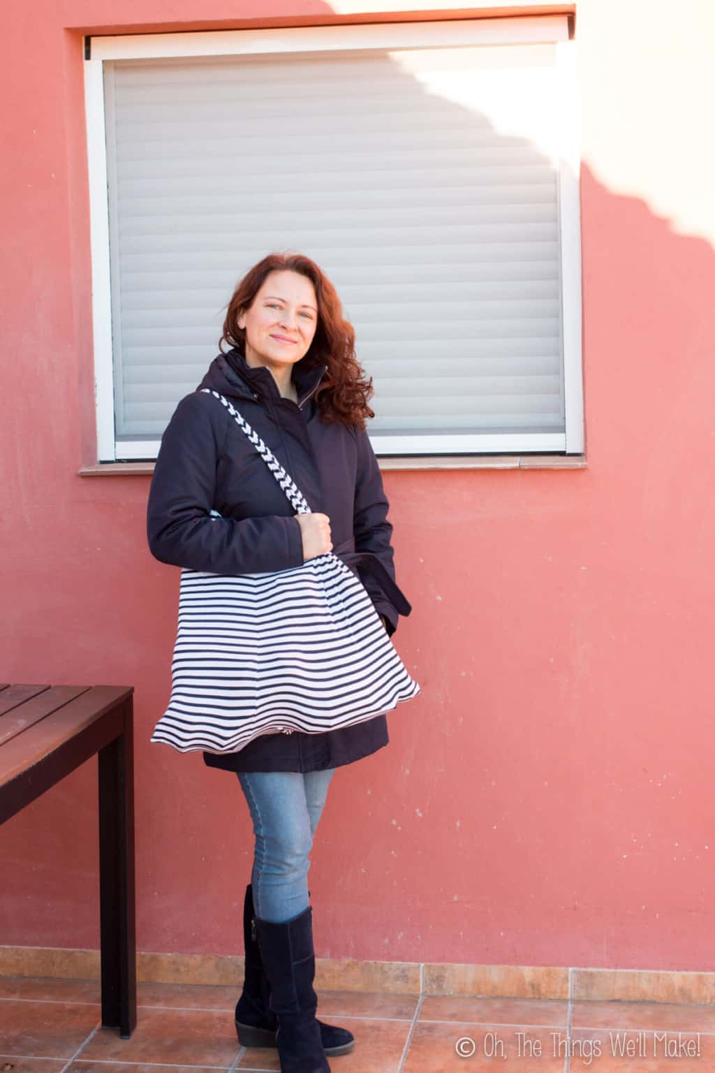 A caucasian woman smiling wearing a navy blue coat and denim jeans with boots, wearing her handmade striped t-shirt bag..