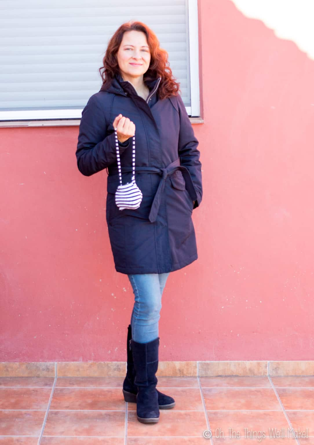 A caucasian woman wearing a navy blue coat, denim pants, and black boots, holding her handmade striped drawstring pouch.