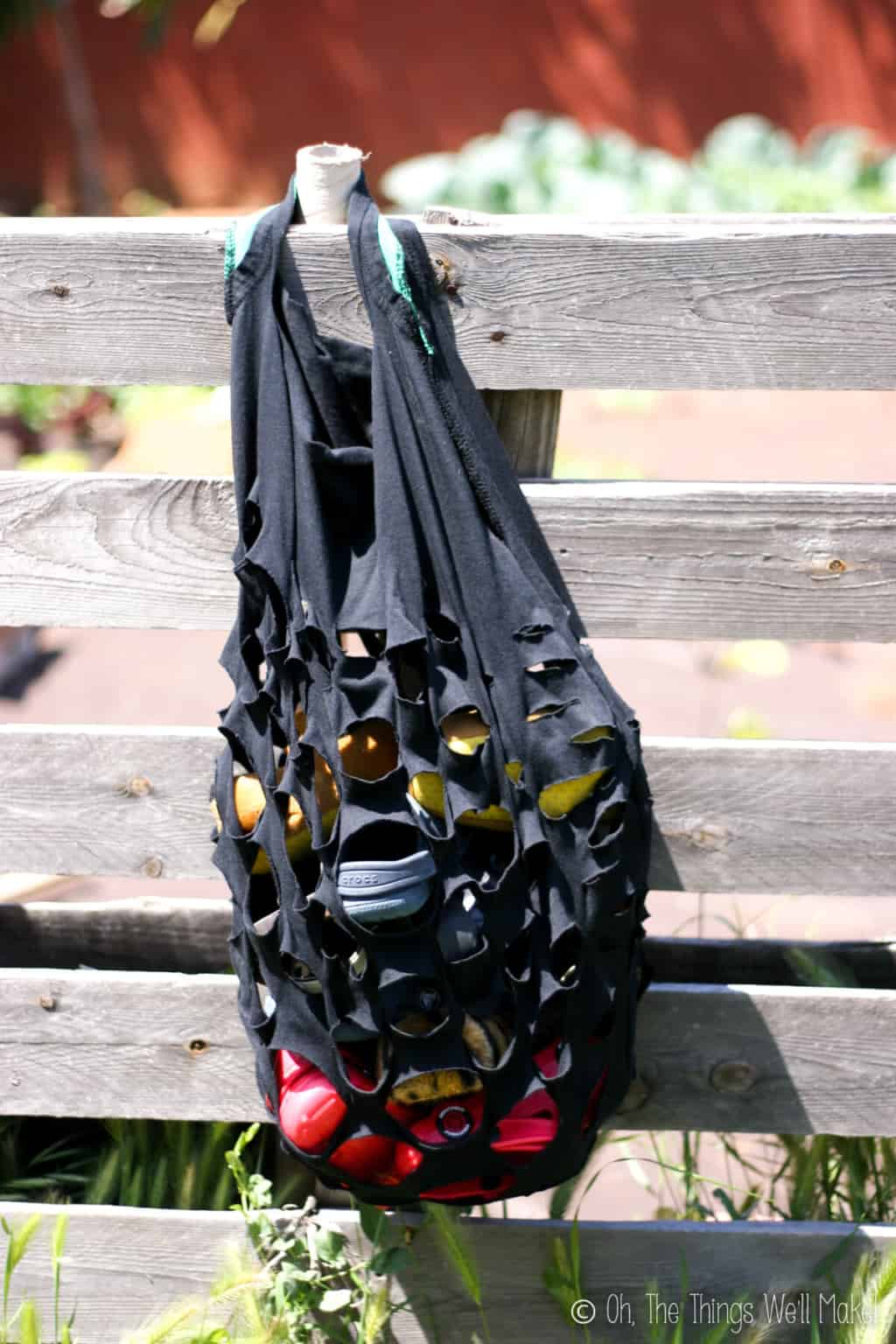 A handmade t-shirt black produce style bag with slits cut into it, filled with beach items hanging on a wood fence.