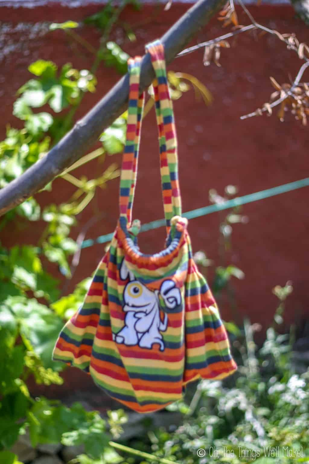 A colorful handmade drawstring backpack made from a baby t-shirt, hanging from a tree branch.