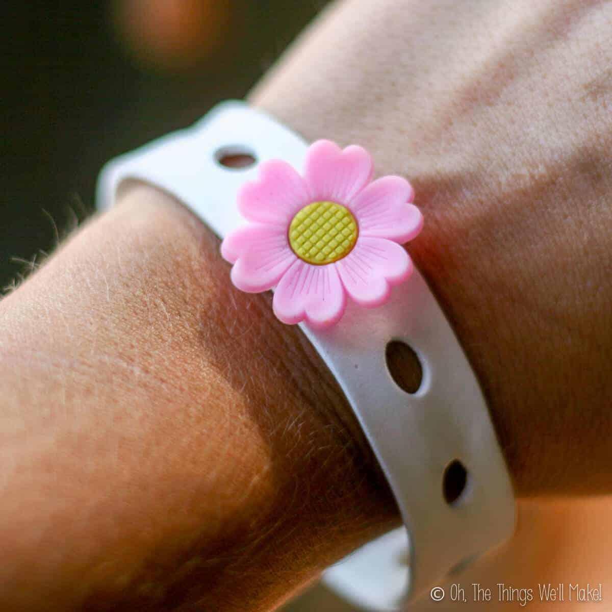 closeup of a girl's wrist wearing homemade craft foam bracelet with flower charm