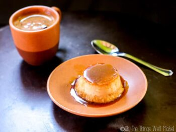 Homemade coconut flan on a plate in front of a cup of coffee