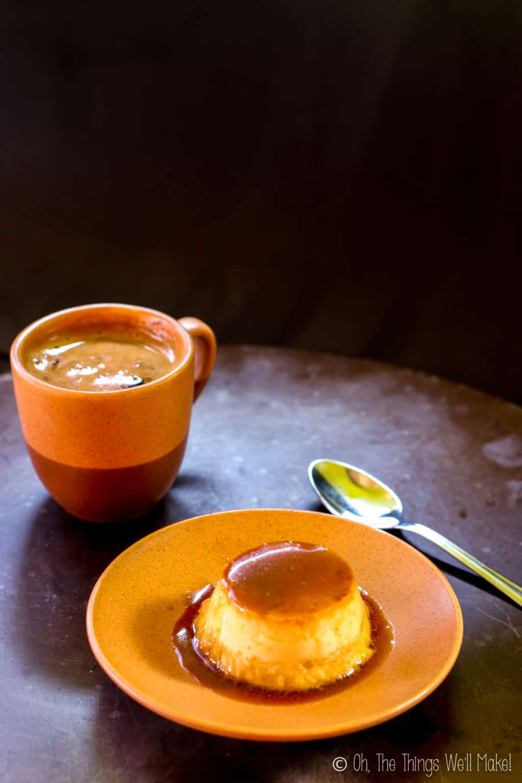 Homemade coconut flan on an orange plate with a silver spoon beside it and a cup of coffee on the other side.