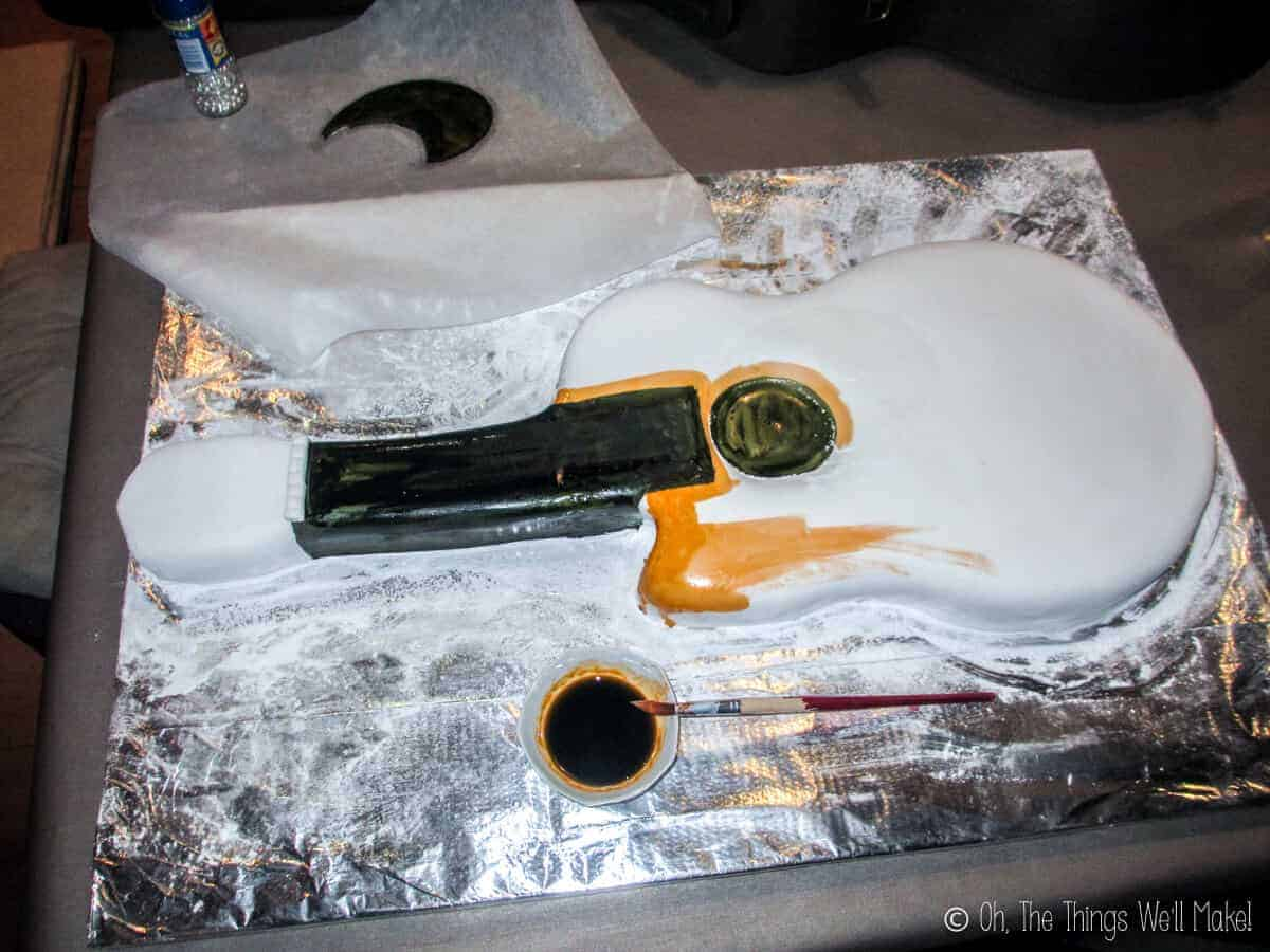 Beginning to paint the fondant guitar with food coloring