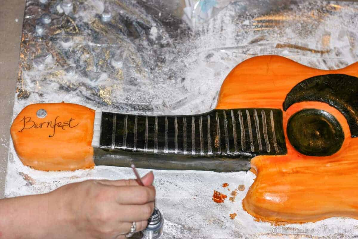 painting on more details to the fondant guitar cake