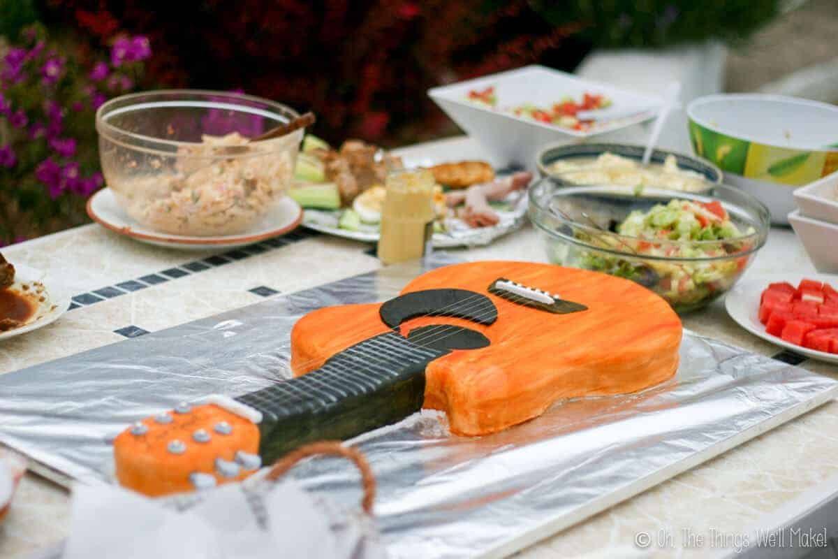 Fondant guitar cake displayed on table with other foods