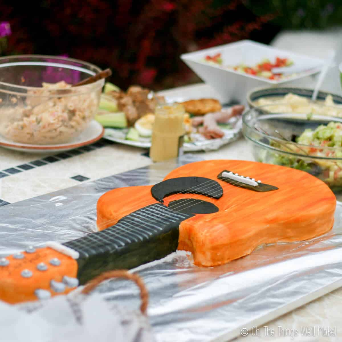 Fondant guitar cake displayed on table with other picnic foods