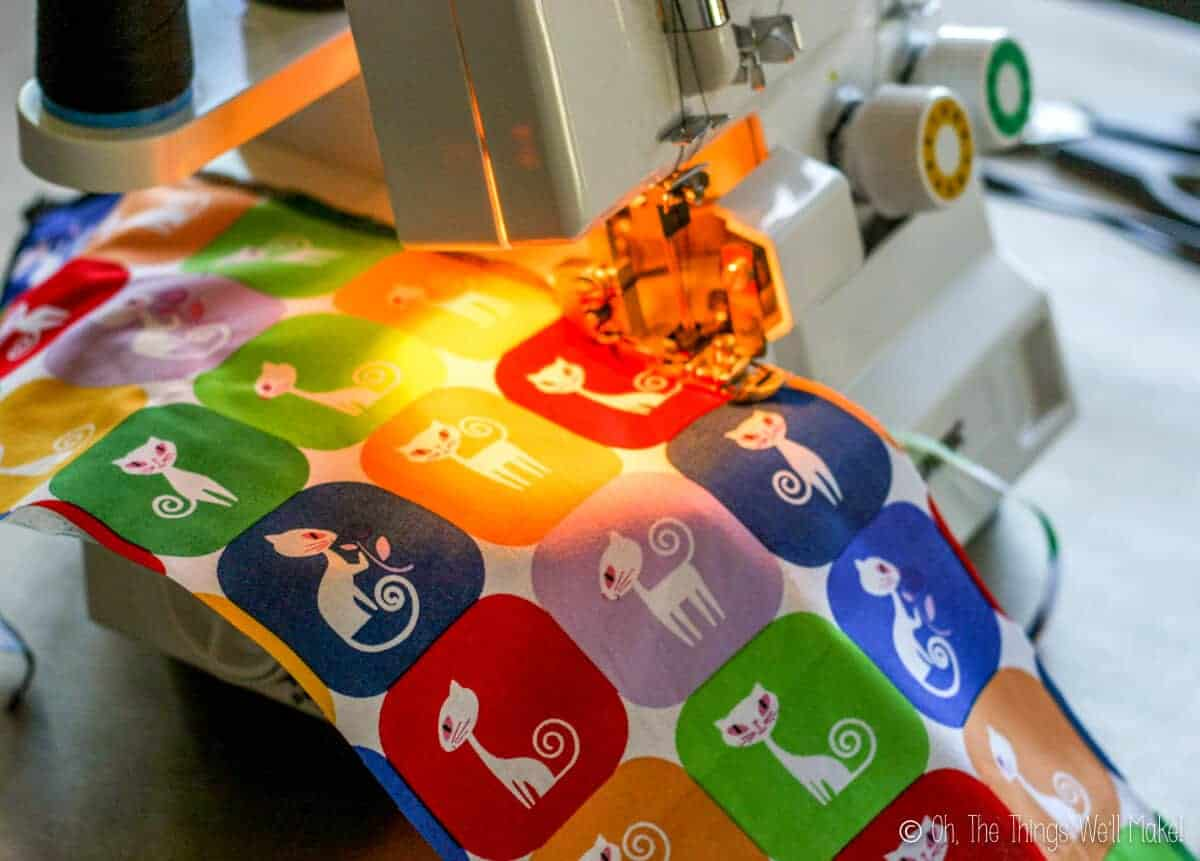 cloth with a colorful design and cats on it in a serger machine