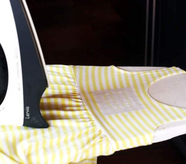 Ironing on a Hello Kitty freezer paper stencil onto a yellow and white striped dress.