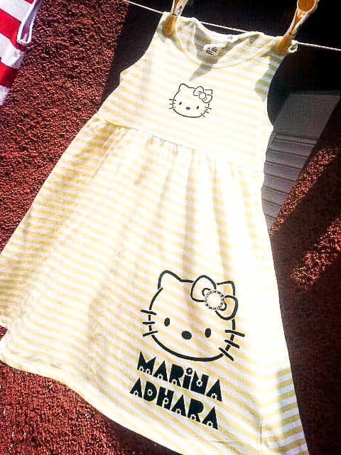 Closeup of a yellow and white striped dress painted with Hello Kitty.