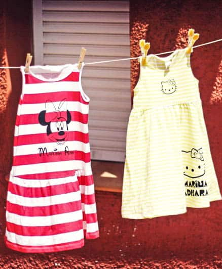 Two dresses hanging on a clothesline. One has been painted with Minnie Mouse and the other with Hello Kitty.