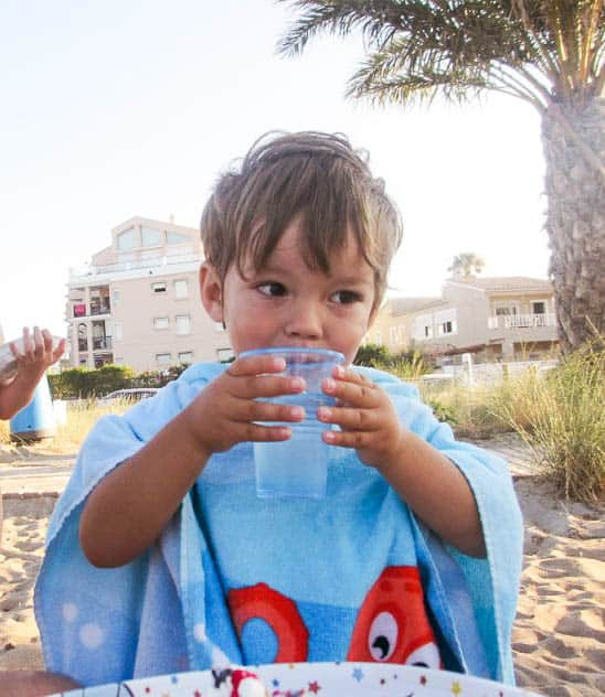 A young boy in a towel drinking water.