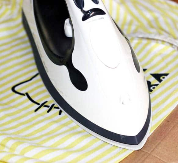 An iron over a painted design on a yellow and white dress.