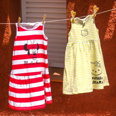 Two dresses hanging on a clothesline. A red and white striped sleeveless dress that has been painted with Minnie Mouse, and a yellow and white striped sleeveless dress painted with Hello Kitty.