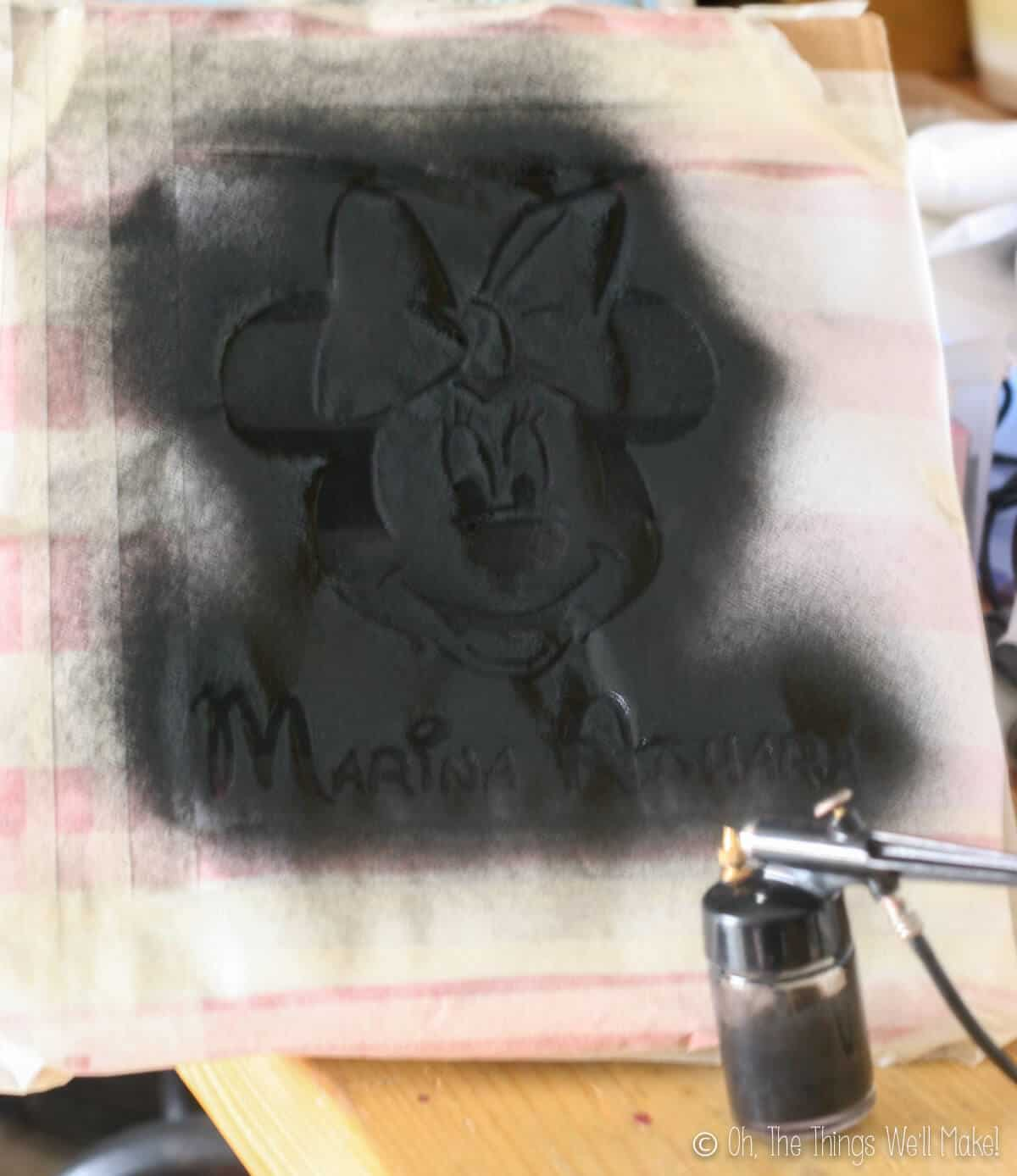 Black fabric paint being sprayed over a freezer paper stencil of Minnie Mouse with an airbrush.