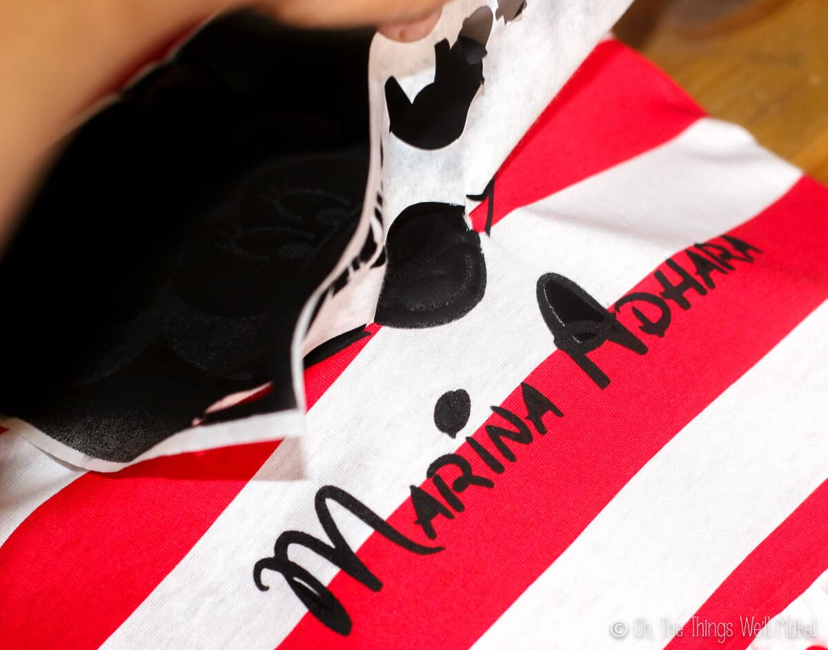 Peeling off a freezer paper stencil, revealing the painted name, Marina Adhara, written in black paint.