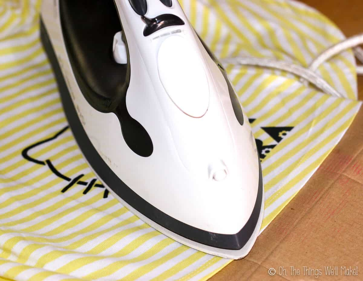 An iron over a painted Hello Kitty design on a yellow and white dress.