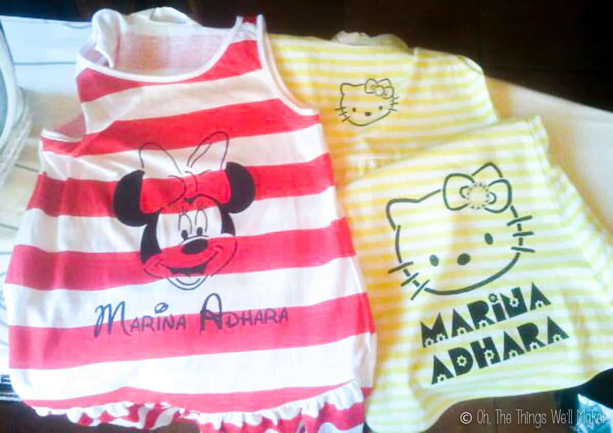 Two dresses placed side by side. On the left is a red and white striped sleeveless dress that has been painted with Minnie Mouse. On the right is a yellow and white striped sleeveless dress painted with Hello Kitty.