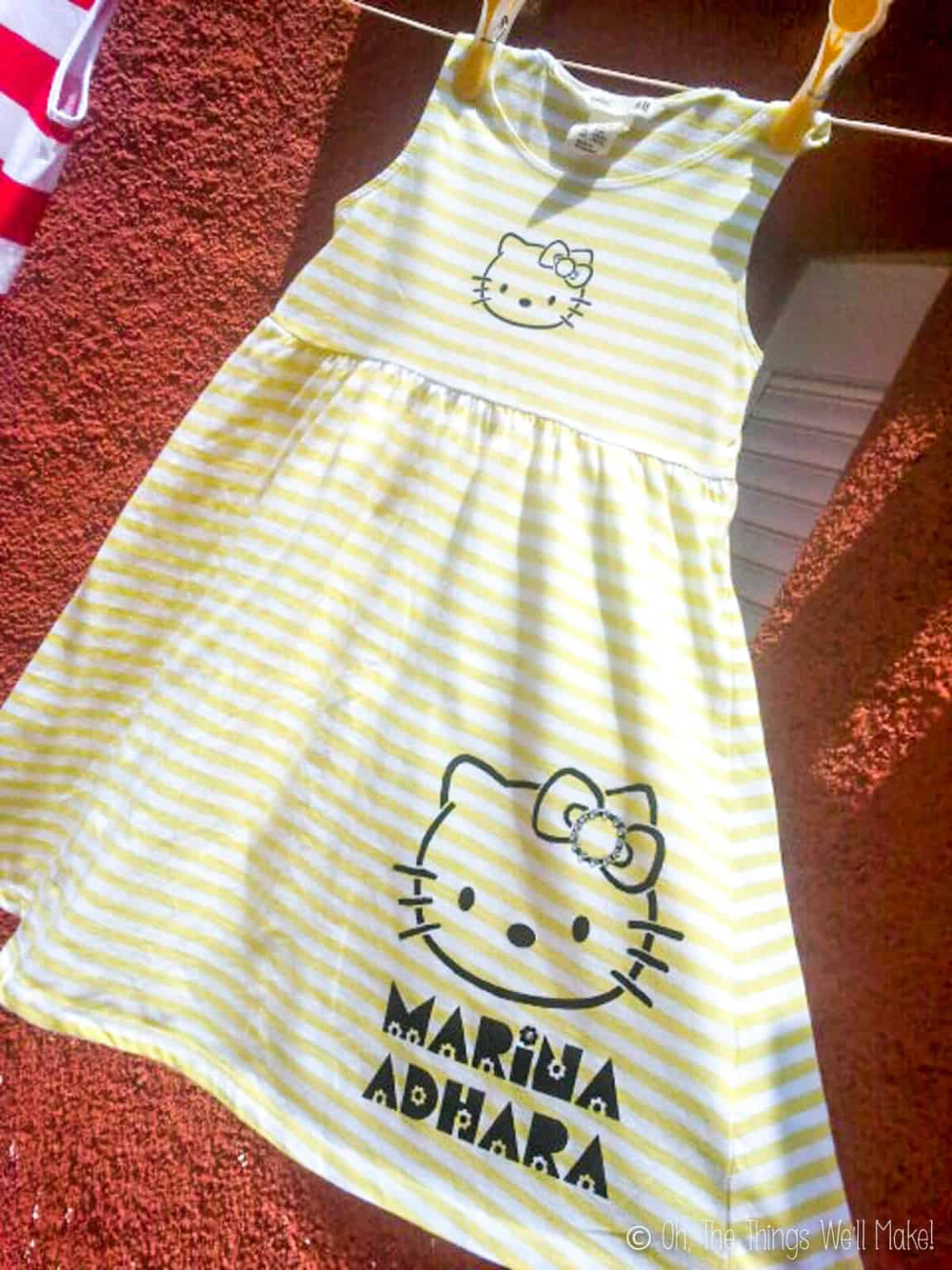 Close up of a yellow and white striped  sleeveless dress painted with Hello Kitty.