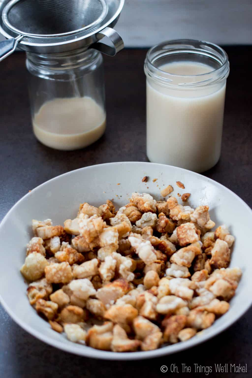 Close up of a white bowl of fried pork cracklings in front of jars of home rendered lard.