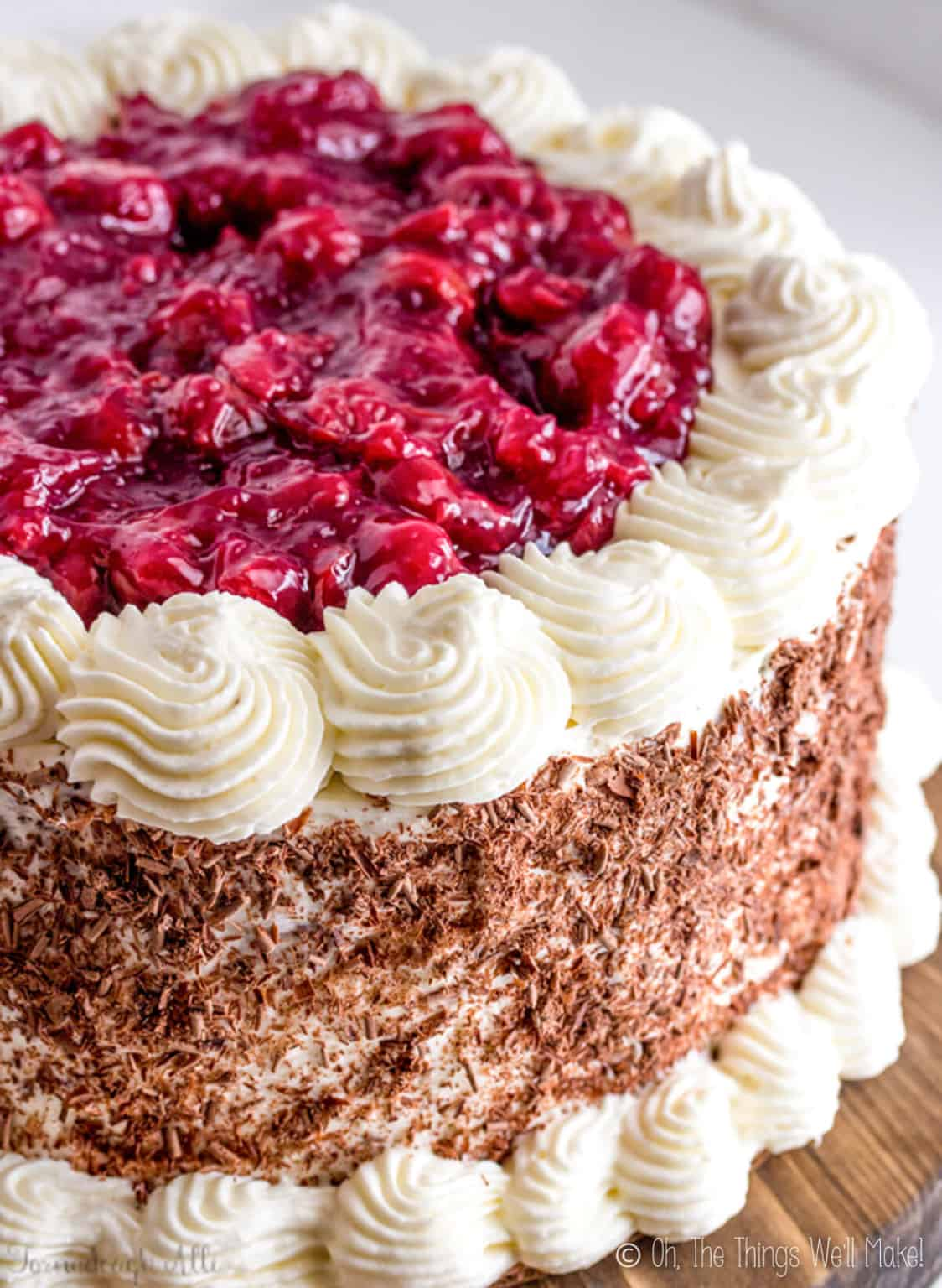 Overhead view of a black forest cake. Red cherries on top, white whipped frosting on the sides, and chocolate shavings on the side.