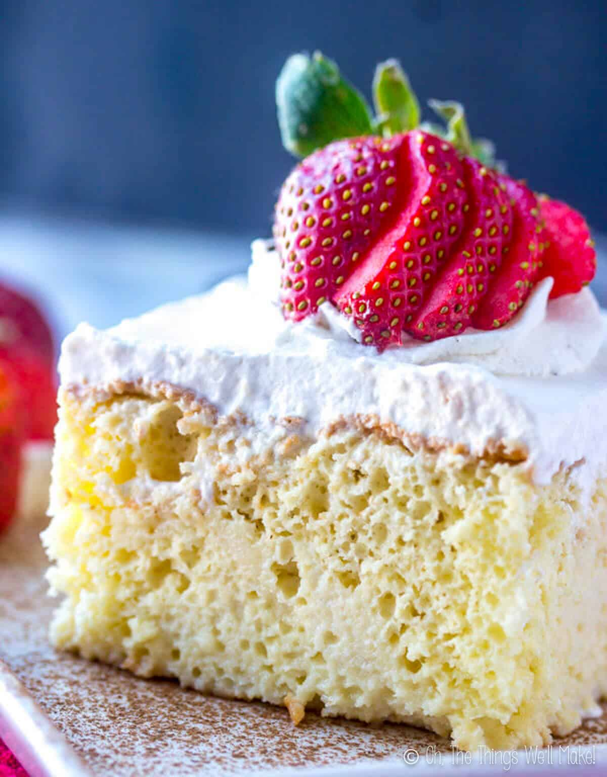 A slice of Tres Leches cake with sliced red strawberries on top.