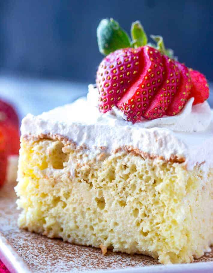 A slice of Tres Leches cake with strawberries on top.
