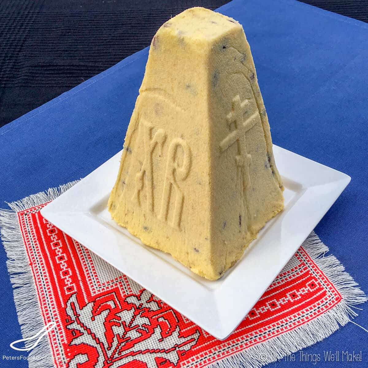 A pyramidally shaped pashka served on a white square plate, which is on top of a red small carpet place mat.