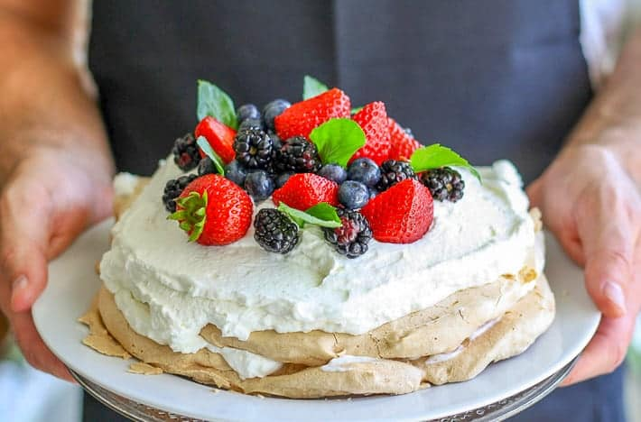 A pavlova, decorated with cream and berries, being held on a plate