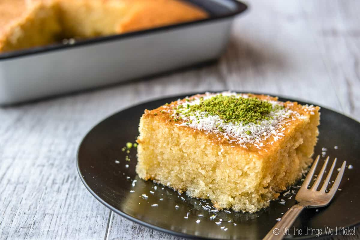 A slice of Greek Revani cake on a black plate, in front of a pan of it.
