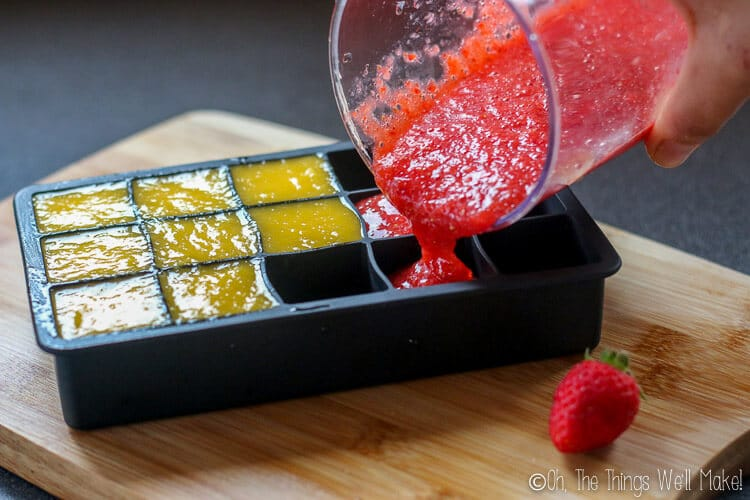 Pouring mango and strawberry purees into an ice cube tray