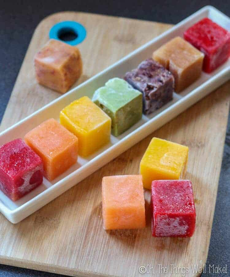 Frozen fruit cubes of different colors on a bamboo cutting board