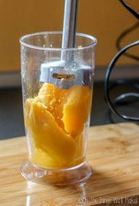 Using an immersion blender to puree the mango