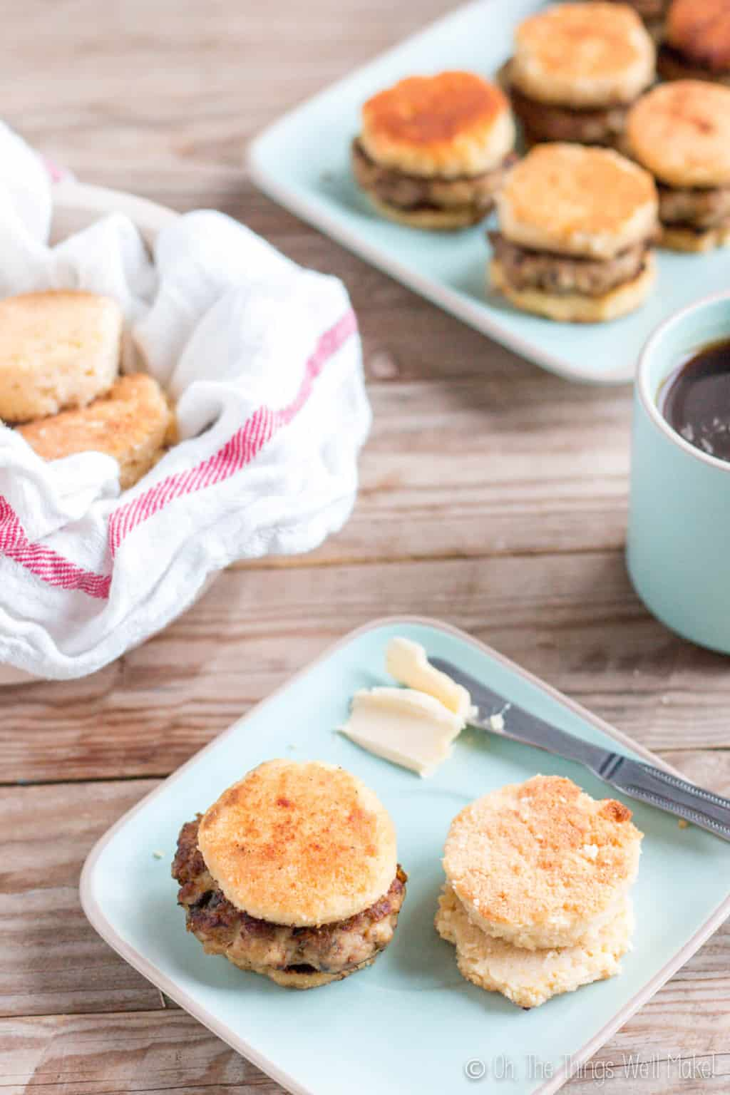 In the foreground, is a light blue square plate with one sausage biscuit and a couple of biscuit pieces next to a knife with butter. On the background is a bowl of biscuits and another plate of sausage biscuits.